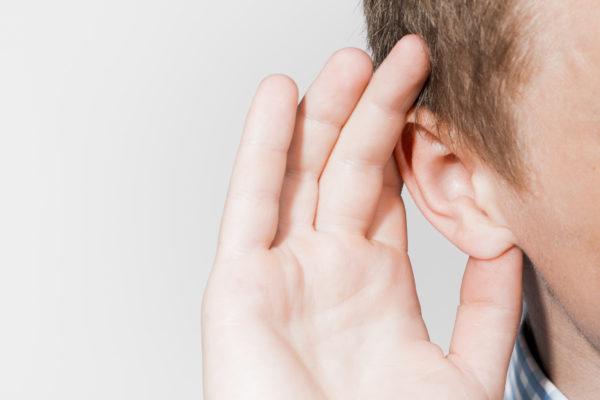 En mann som holder handa bak øret for å høre bedre