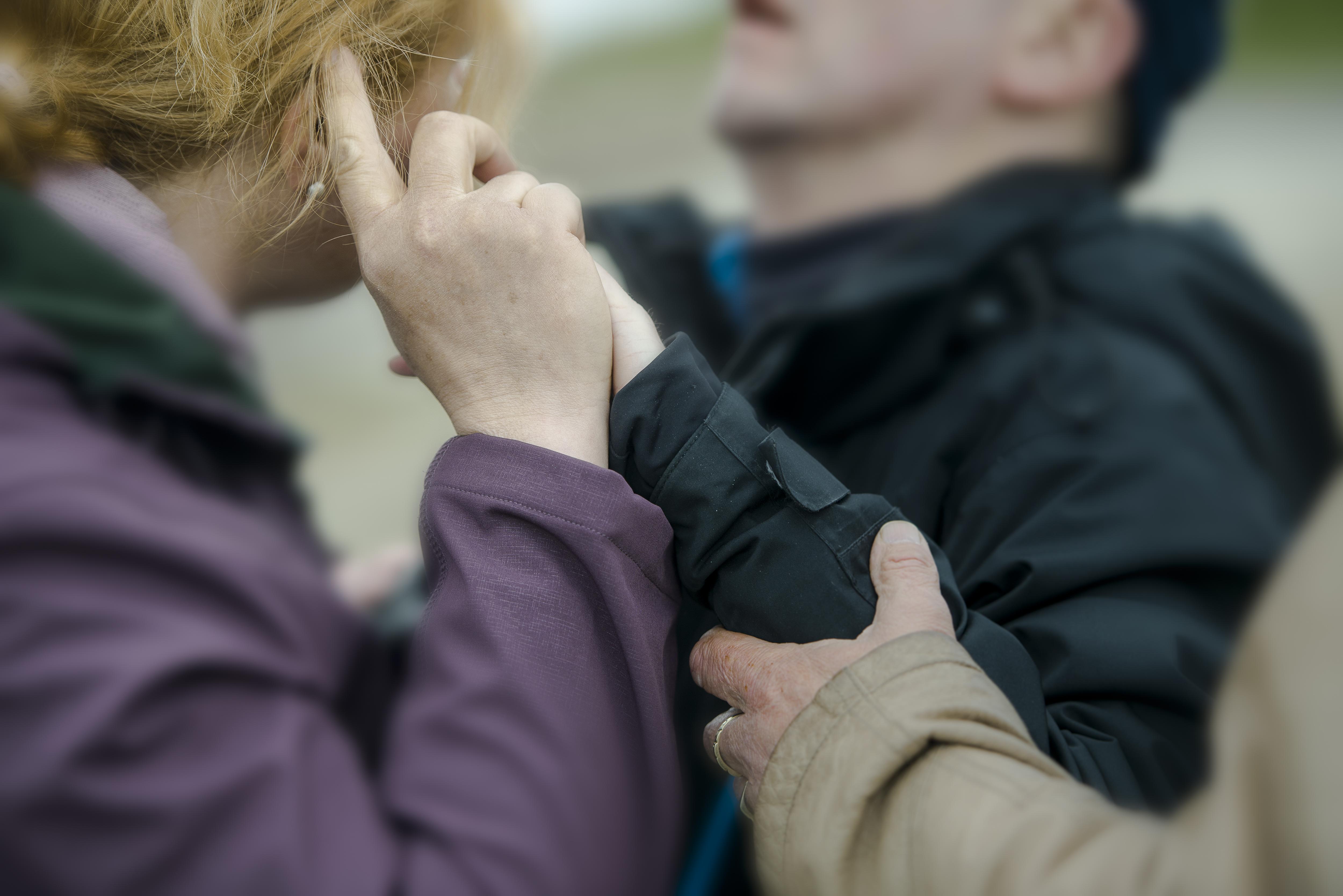 Person som holder hånden til en døvblind opp mot ansiktet