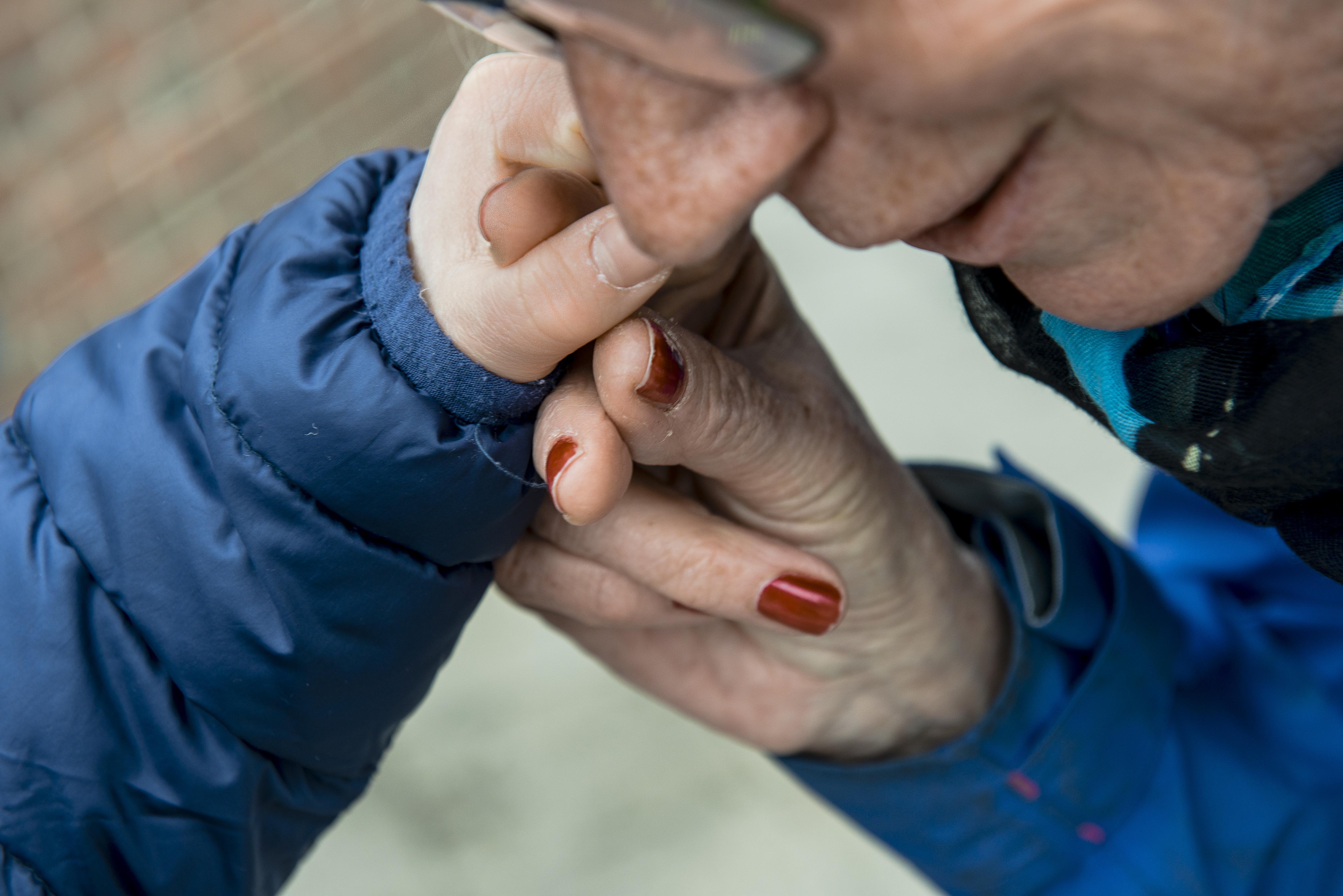 Barnehånd som holder en voksen sin hånd og stryker den voksne kinnet